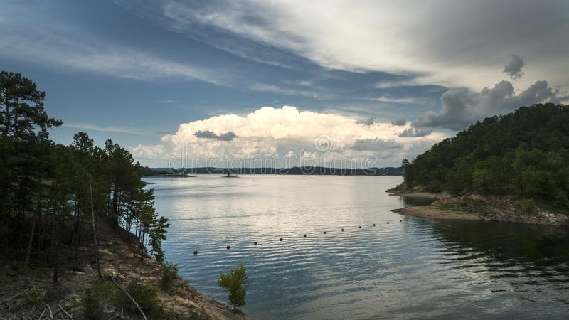 Storms approaching a beautiful lake with hills. Stormy weather is approaching a serene lake with hills, islands, trees and bouys. Broken Bow Lake in southeastern stock photography