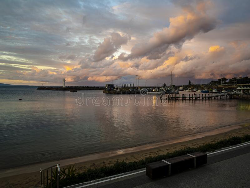 Storms clouds form off the coast of Wollongong Harbour. Sunset royalty free stock image
