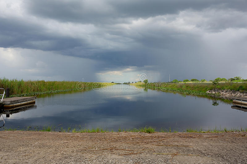 Storms Colliding. 2 heavy rain storms set to collide, view from water canal in the Florida Everglades royalty free stock photo