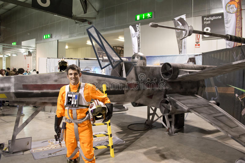 X-Wing pilot at Cartoomics 2014. A cosplayer dressed with Starw Wars rebel pilot uniform poses in front of an X-Wing reproduction during the Cartoomics 2014 royalty free stock photo