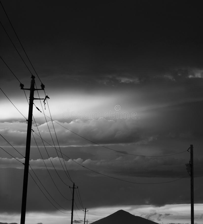 Stormy glow in the clouds. Sky and clouds lit up with a glow after a heavy rain storm at sunset over Black Butte and roadside power lines in Central Oregon on a stock photos