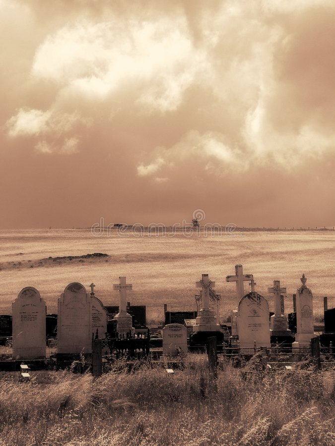 Stormy Graves. An old graveyard lays amongst fields of Barley with a stormy sky (sepia tonings royalty free stock images
