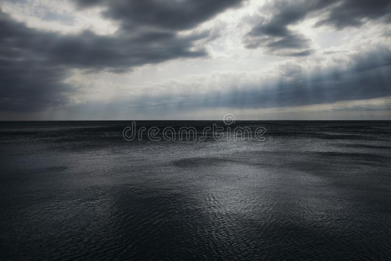 Stormy gray-blue sea and sky in the clouds and rays of the sun. royalty free stock photo
