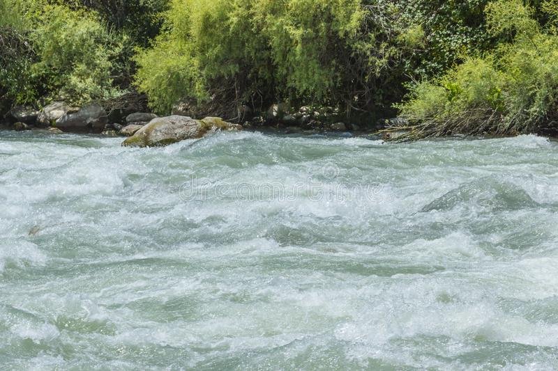 Stormy mountain stream. The game of splashes and waves near the stones. royalty free stock photography