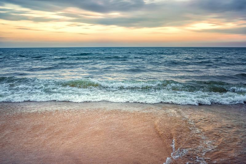 Stormy ocean and sandy shore. On the background of the sunset royalty free stock image