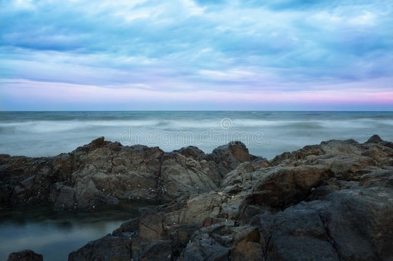 Stormy ocean and stony shore stock images