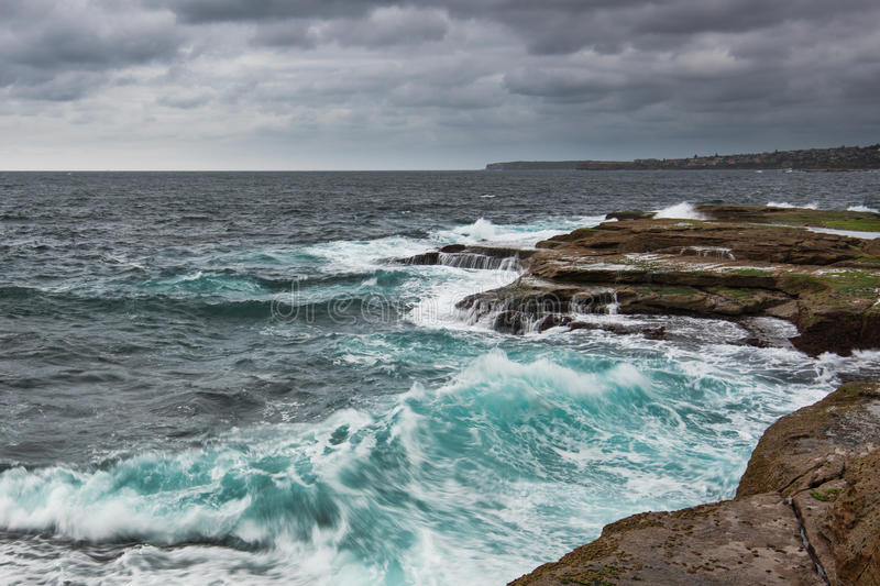 Stormy Ocean with unrest sea and waves. Stormy ocean in Sydney with gray heavy clouds and unsert sea with white foam and cyan color royalty free stock photo
