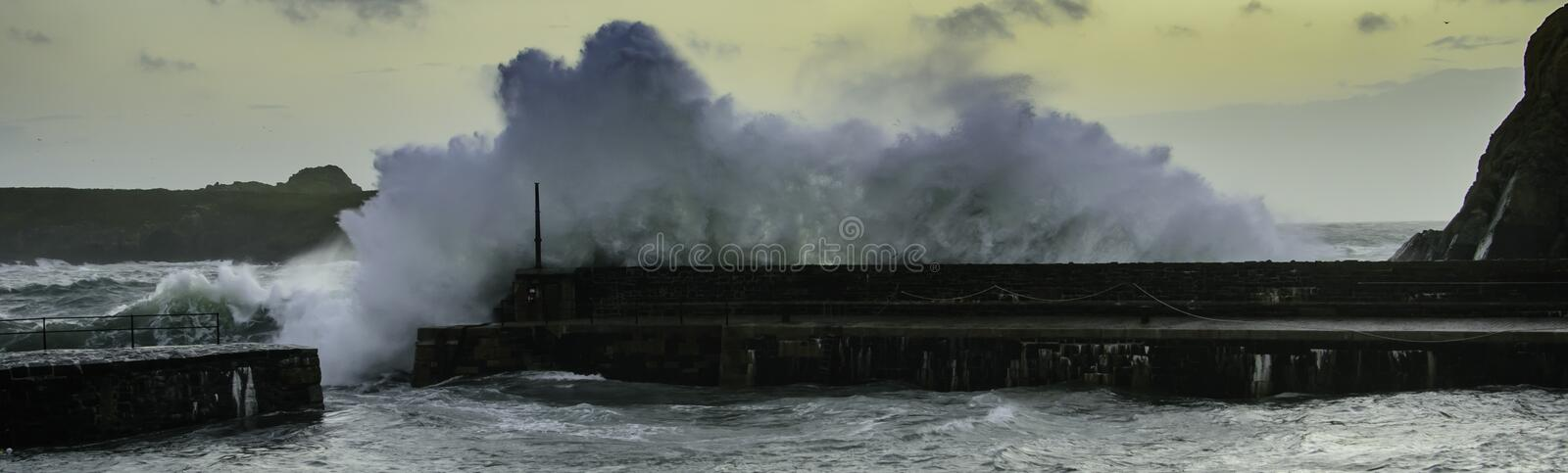 Stormy ocean waves crash over harbour wall. Waves crashing over a harbour wall in Mullion Cove, Cornwall