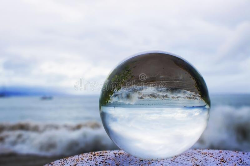 Surf and Beach Taken Through Glass or Crystal Ball. Stormy ocean with waves crashing on beach taken in reflection in glass ball stock photo