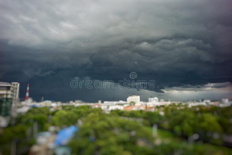 Stormy raining cloud cover the city with heavy rain and wind. Dark cloud comes to the town with blurred trees in foreground stock photography