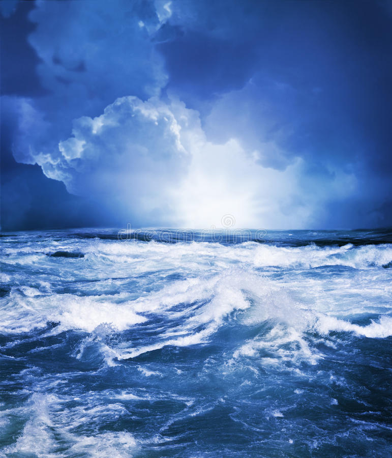 Stormy sea. A rough ocean with white caps and a stormy sky as a bright light appears from the horizon