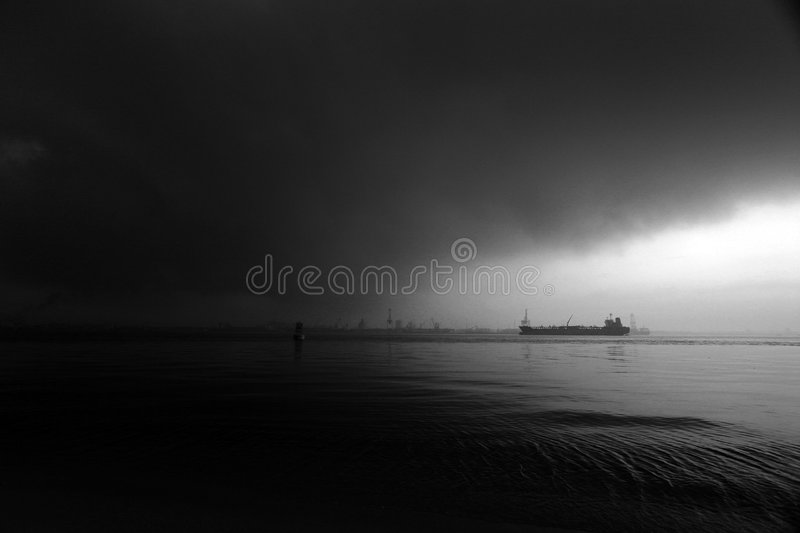 Stormy drama sea sky with ship. Sail into ocean storm waters - A dramatic nature landscape picture of a ship vessel sailing headlong into pitch dark stormy rain royalty free stock images
