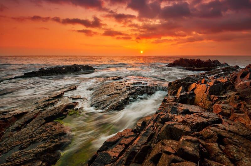 Stormy sea at sunrise. Waves splash on rock at sunrise