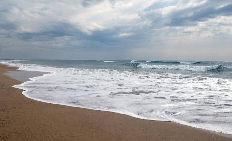 Stormy sea waves breaks about empty beach under cloudy sky. Landscape with stormy sea waves breaking about the empty wild sandy beach against the cloudy sky on stock photos