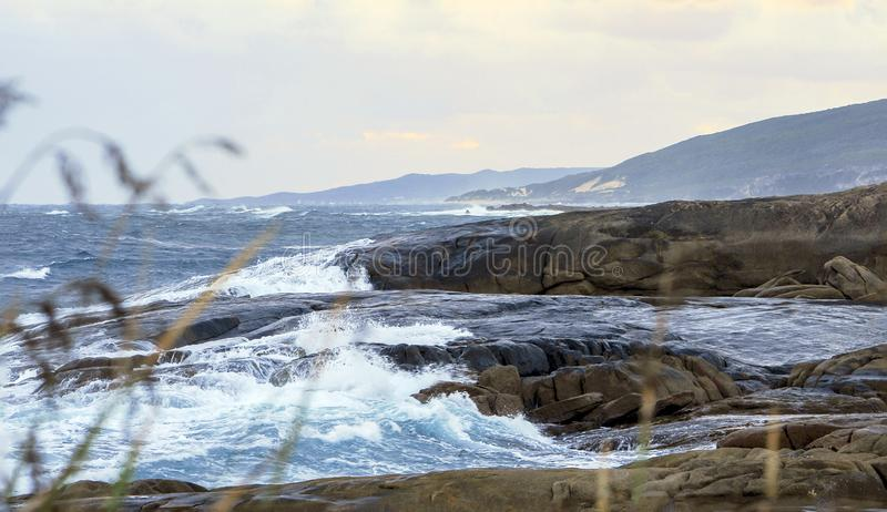 Stormy seas as waves crash into large granite boulders, with mountains in the distance. royalty free stock photo