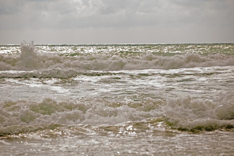Stormy seascape with cloudy sky and waving sea surf on wet brown sand. Green sea water with white foam waves and dark royalty free stock photo