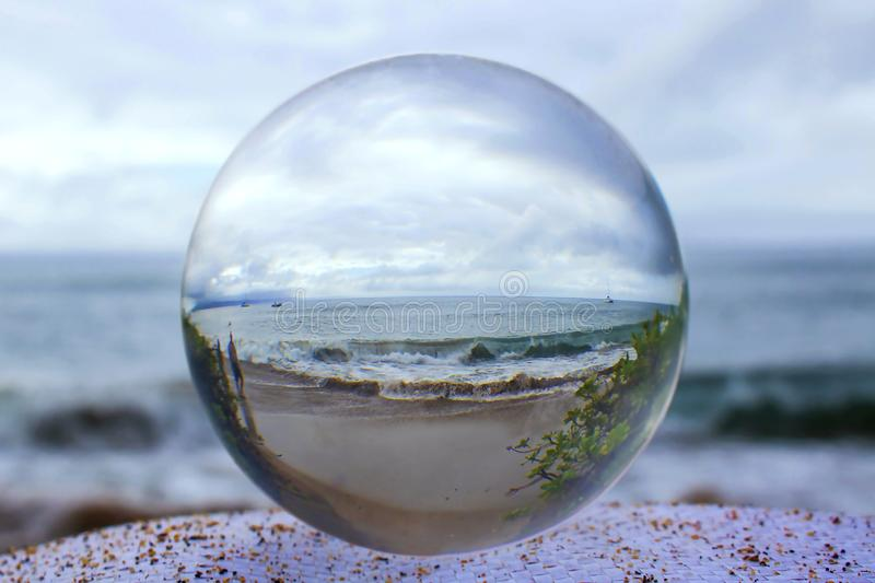 Stormy shore captured in Glass or Crystal Ball. Beach with green ocean taken through glass or crystal ball stock photography
