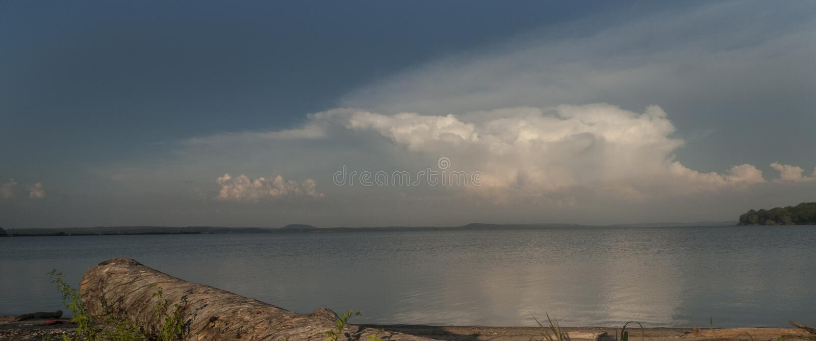 Stormy skies over a lake with driftwood on shore stock photos