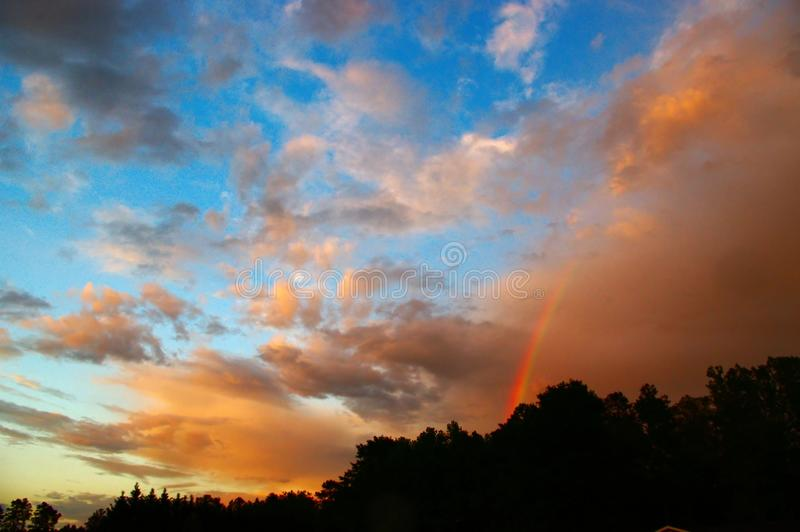 Stormy Skies with a Rainbow. After a storm passes, the skies fill with colored clouds, multiple hues, and rainbows stock images