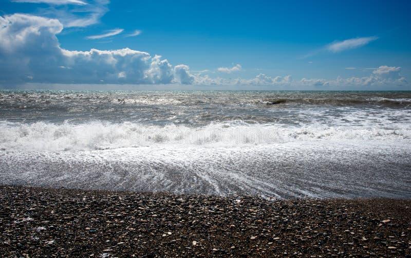 Stormy Sky e oceano ondulado com ondas atingindo a costa cheia de seixos foto de stock