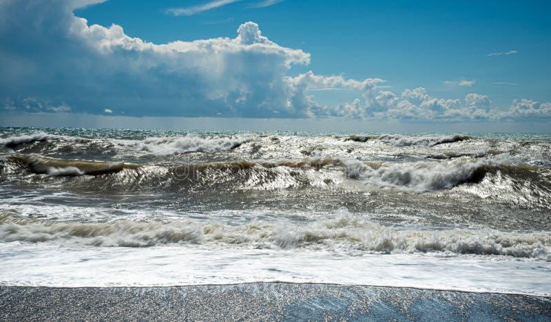 Stormy Sky e oceano ondulado com ondas atingindo a costa cheia de seixos imagens de stock