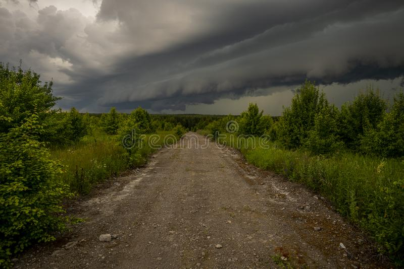 Stormy sky, low thunderclouds hanging over the dirt road leading into the forest royalty free stock image
