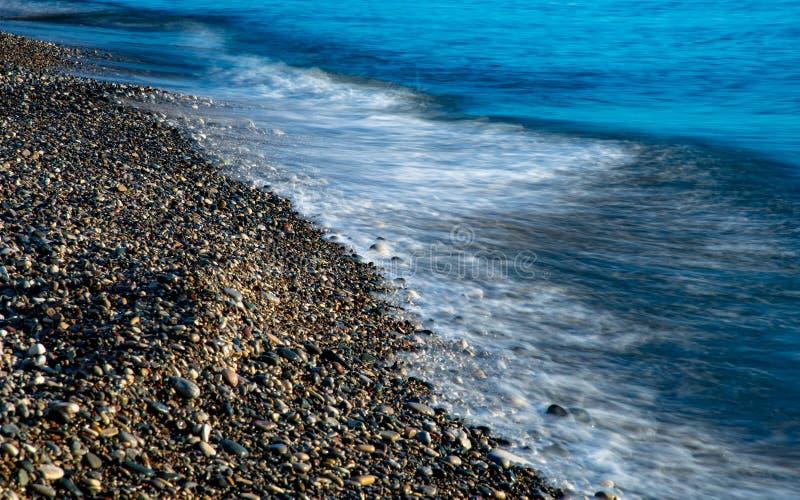 Stormy Sky och Wavy Ocean med vågor som slår mot kusten full med vackra småstenar royaltyfri bild