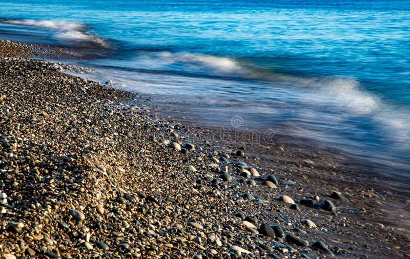Stormy Sky och Wavy Ocean med vågor som slår mot kusten full med vackra småstenar arkivbilder