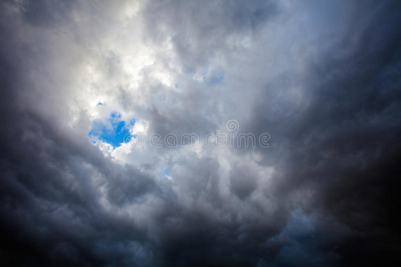 Stormy sky opening. Dark stormy sky opening showing a hole with bright blue sky stock image
