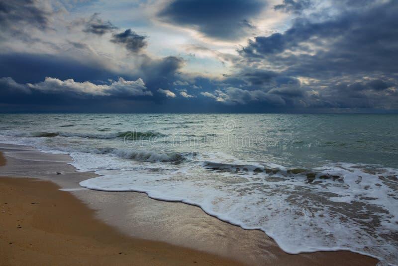 stormy sky over sea and sandy beach stock photos