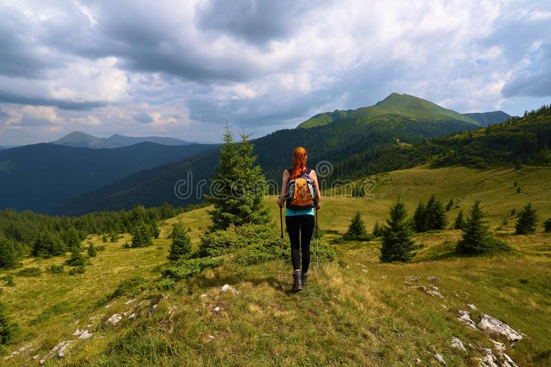 Stormy, thundery sky. The view with the peaks of mountain. Sporty red hair girl climbs up to the hill with rocks. Extreme sport. stock images
