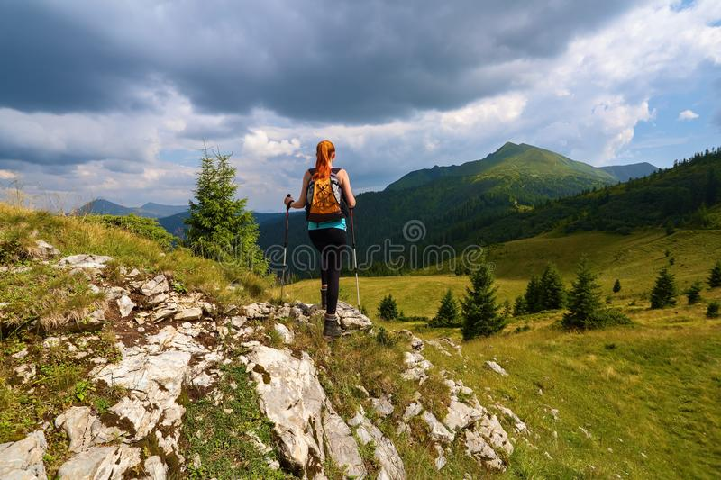 Stormy, thundery sky. The view with the peaks of mountain. Sporty red hair girl climbs up to the hill with rocks. Extreme sport. royalty free stock photography