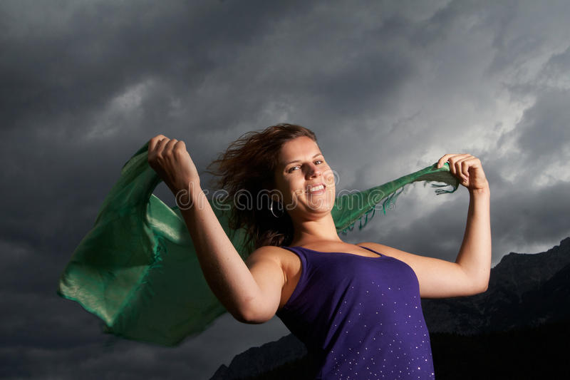 Stormy times. Young woman in the middle of a storm. She is holding a green fabric in the wind stock image
