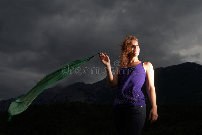 Stormy times. Young woman in the middle of a storm. She is holding a green fabric in the wind stock photos