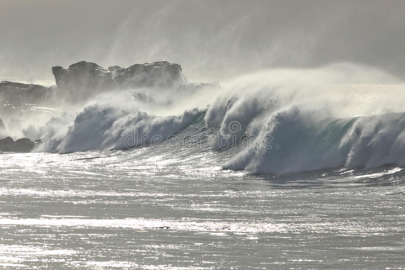 Stormy waves against dangerous cliff at noon. Portuguese northern coast stock photo