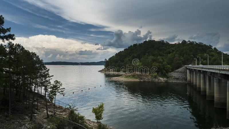 Storms approaching a beautiful lake with hills, Dam. Stormy weather is approaching a serene lake with hills, islands, trees and bouys. Broken Bow Lake and Dam in royalty free stock photos