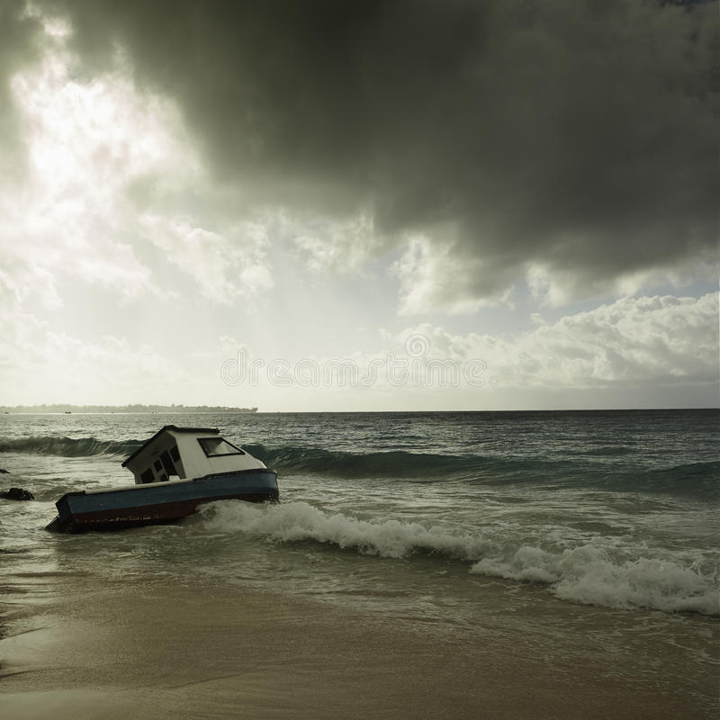 Stormy weather and fishing boat stranded on a beach royalty free stock photography