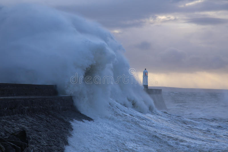 Stormy weather at Porthcawl lighthouse, South Wales, UK. Huge Waves crash over Porthcawl lighthouse, South Wales, UK, in a severe storm stock images