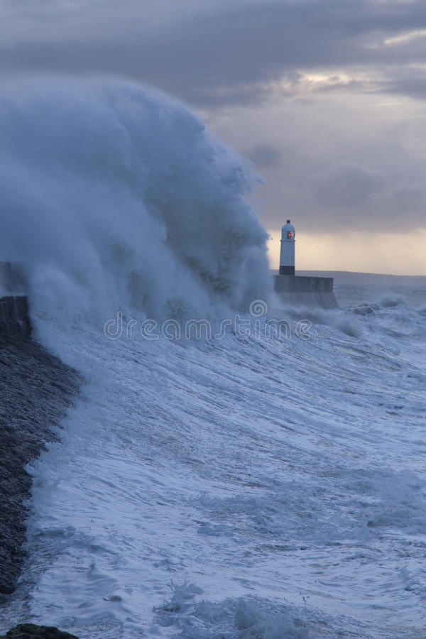 Stormy weather at Porthcawl lighthouse, South Wales, UK. Huge Waves crash over Porthcawl lighthouse, South Wales, UK, in a severe storm royalty free stock image
