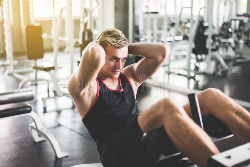 Storng man doing situp or crunches in gym,Men exercise muscular stomach stock photography