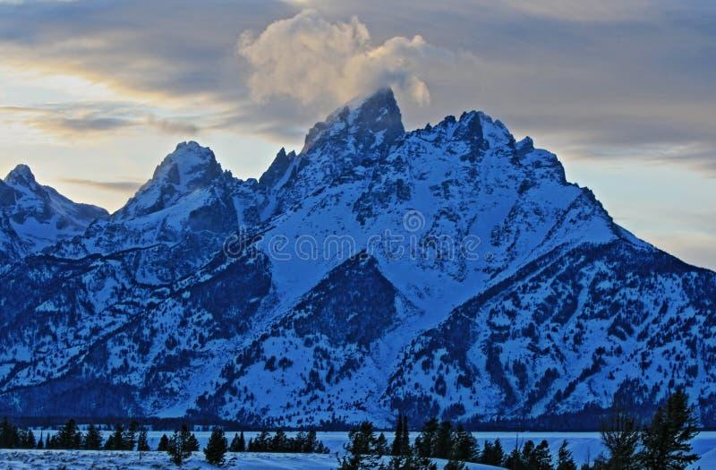 Storslagna Tetons på alpenglowskymningsolnedgången under linsformade moln i den storslagna Tetons nationalparken i Wyoming arkivfoton