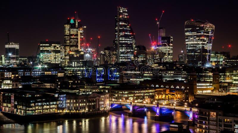 Storstaden står högt på natten med ljus och reflexioner i floden arkivbilder