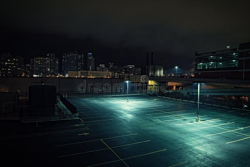 Stort öde stads- stadsparkeringsplats och garage på natten arkivbilder