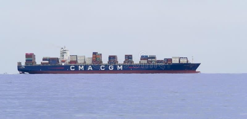 Stort behållarelastfartyg som lämnar port, når att ha laddat lastande av operationer royaltyfri fotografi
