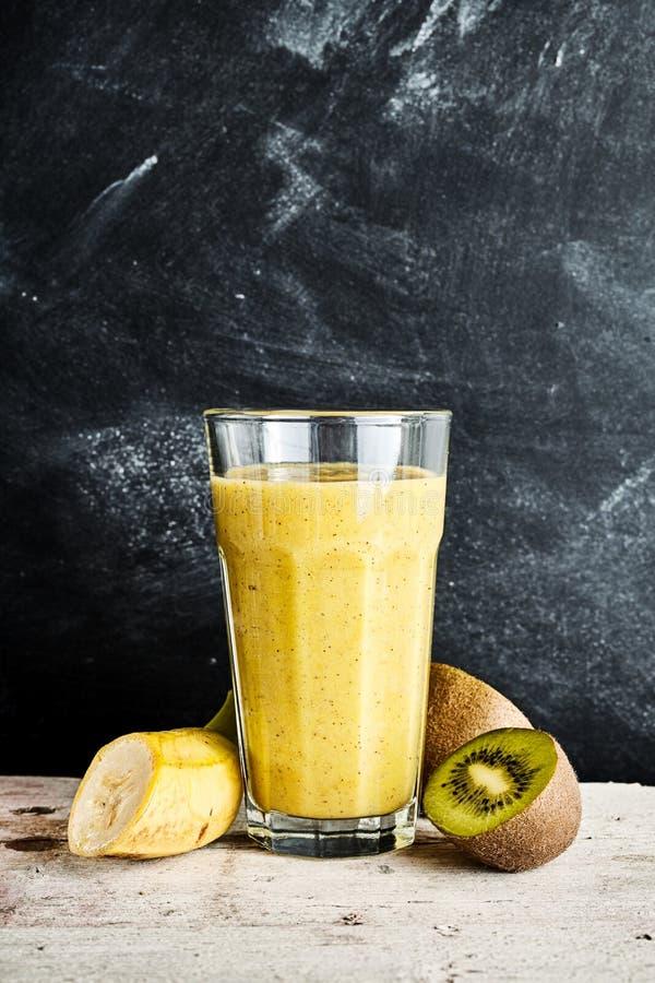 Stort exponeringsglas av kiwi- och banansmoothien arkivbild