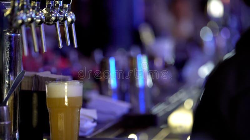 Stort exponeringsglas av nytt kallt öl med den väntande på mannen för skummigt vitt skum beställde det arkivbilder