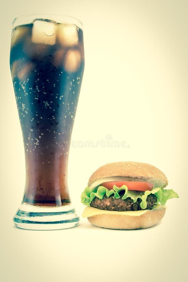 Stort stort exponeringsglas av popsodavatten med den frodiga smakliga hamburgaren på en vit bakgrund Tappning retro stilfoto för  arkivfoto