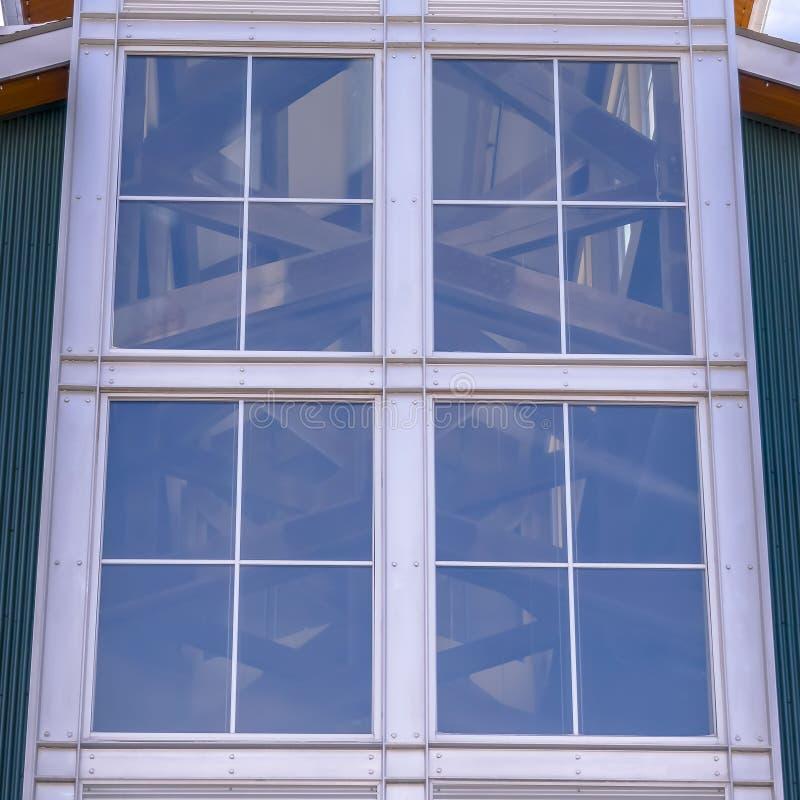 Stort exponeringsglasfönster för klar fyrkant av en byggnad med en ljus och molnig bakgrund för blå himmel arkivbilder