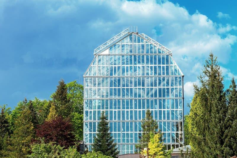 Stort exponeringsglasväxthus i botanisk trädgård vid blå himmel arkivbilder