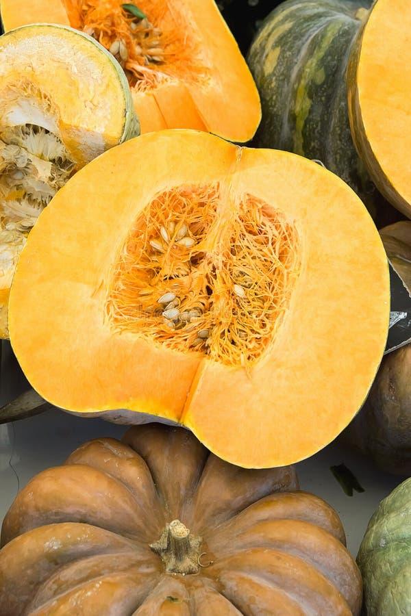 Stort färgrikt härligt mörker - apelsin- och gräsplanpumpor som är hela och halveras Bucklatexturfrö Fyrkantig sammansättning tac arkivfoto